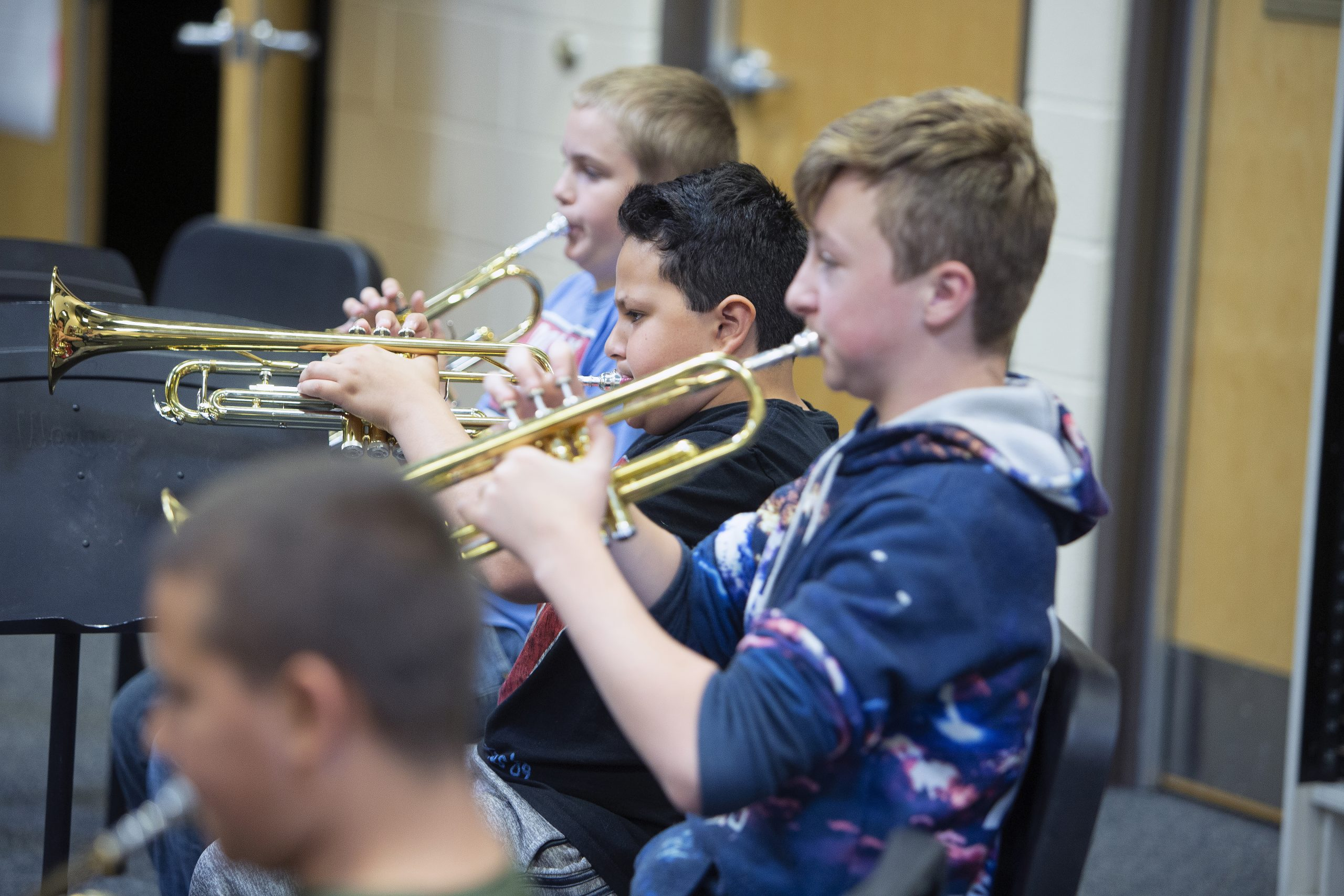 Three male students playing trumpet