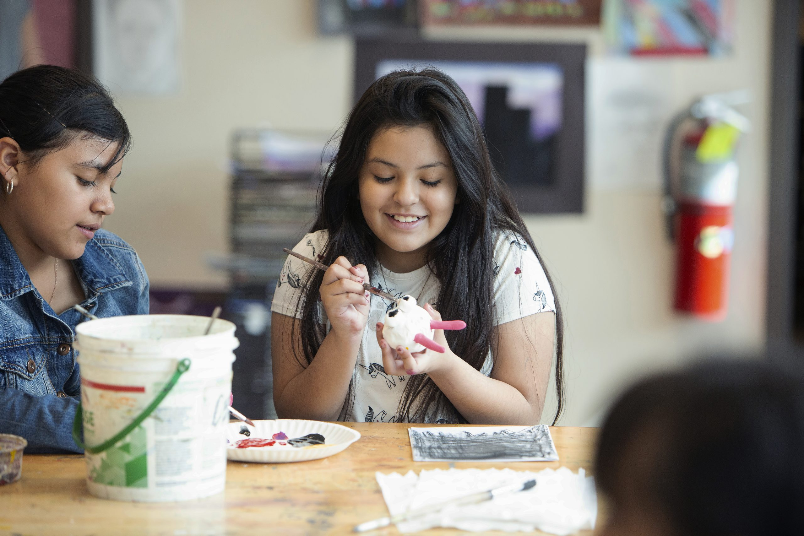Two female students painting and smiling
